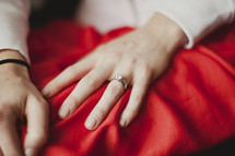 A woman displays her engagement ring on her left hand.