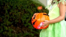 a girl child in a costume holding a jack-o-lantern trick-or-treating on Halloween
