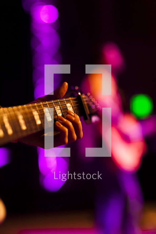 Hand holding guitar with other player in background on lighted stage fret board
