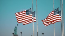 statue of Liberty and American flags on flagpoles at half staff