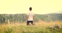 young man kneeling in prayer on a mountaintop