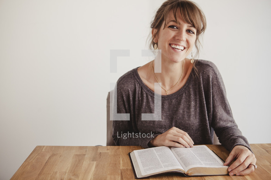 A young woman smiling as she reads her Bible