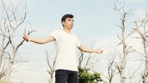 young man praying outdoors with outstretched arms