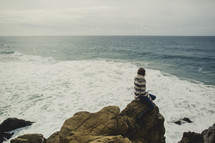 woman sitting on the rock looking out over the ocean