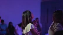 a woman praying during a worship service