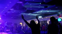 silhouettes with raised hands at a worship service