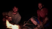 men sitting by a campfire playing music