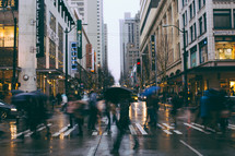 People with umbrellas walk across a rainy city street.