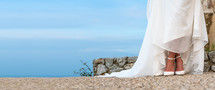 Woman in wedding dress with white shoes outdoors