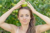 a young woman with a green apple on her head