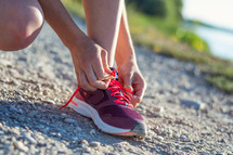 a woman tying her shoe laces before a jog