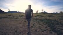 a woman walking across a prairie