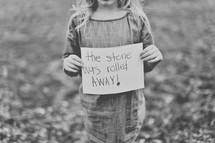 """A girl holding a paper reading, """"the stone was rolled away!"""""""