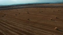 aerial view over hay bales in a plowed field