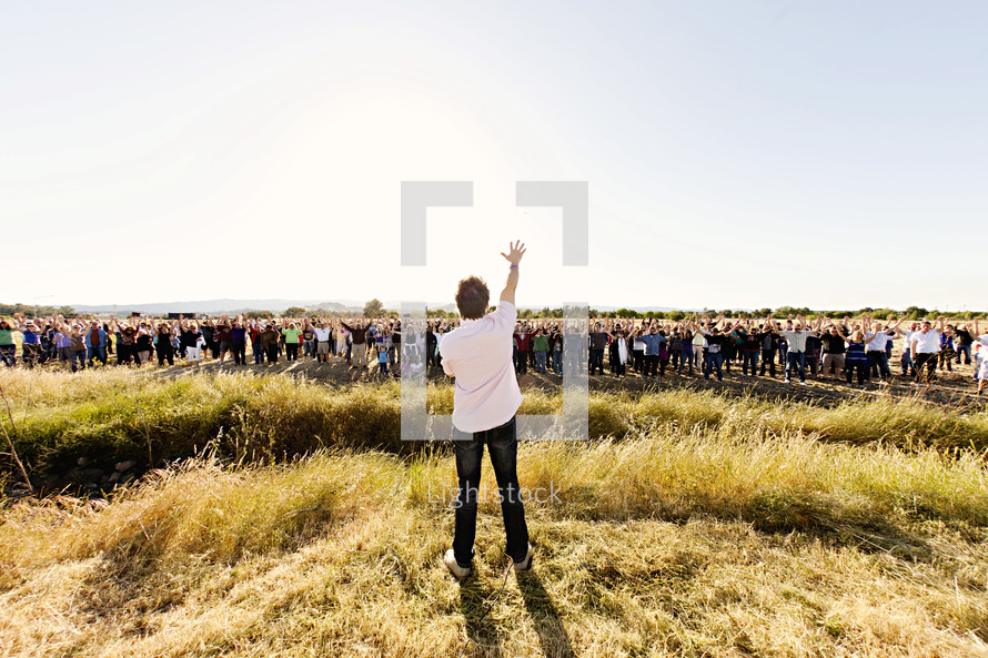 A man speaking to a crowd of people in a field, with his arm raised prayer proclamation land  leadership, new beginnings, church construction, pray on the property, new land.