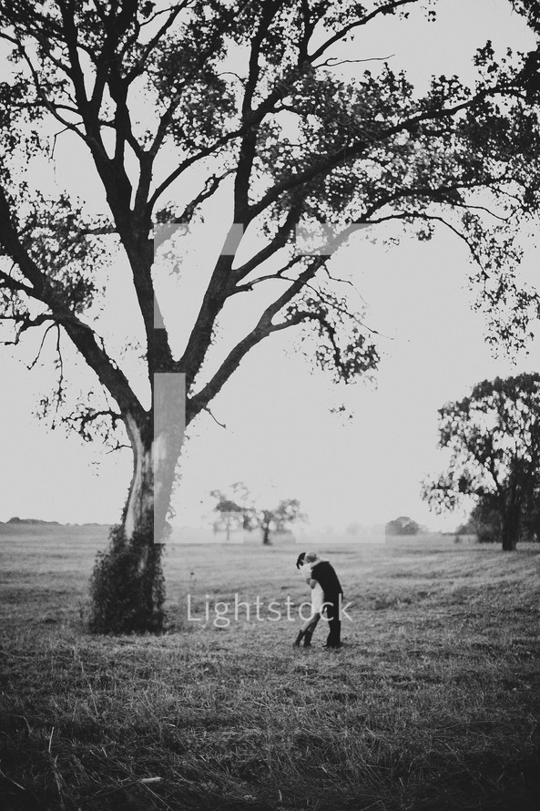 man and woman hugging under a tree