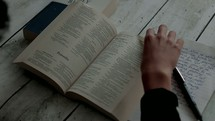 a teen reading a Bible and taking notes