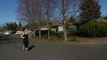 A young woman jogging down a residential street.