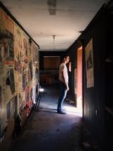 man standing in the sunlight at an open doorway