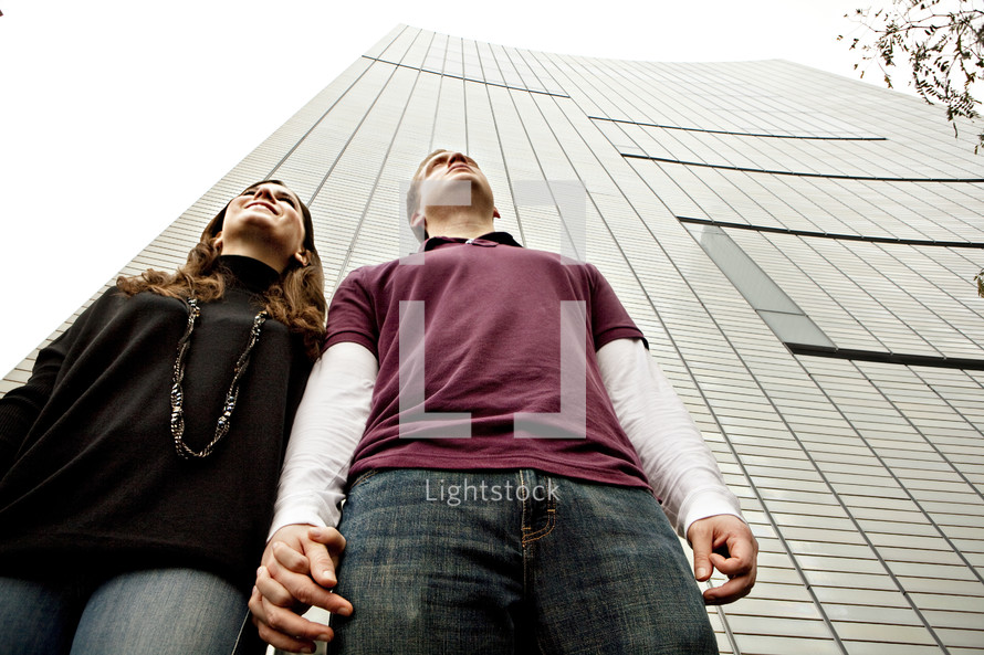 Couple holding hands in front of skyscraper building