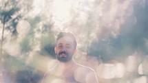 A man standing outdoors under intense sunlight.