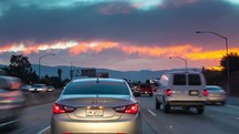 Hyperlapse of stop-and-go traffic at sunset on the California 91 Freeway near Los Angeles.   Headlights and brake lights from the cars add to light from the dramatic sky.