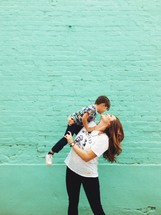 Woman holding a child while standing in front of a brick wall.