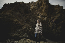 woman standing in front of rocks on the beach