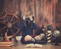 a little girl holding a camera and a nautical travel scene