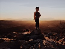 Silhouette of a child standing atop a rock in front of a mountain range at dusk.