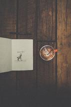 December deer card and a mug of cappuccino