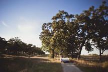 A convertible driving down a dirt road