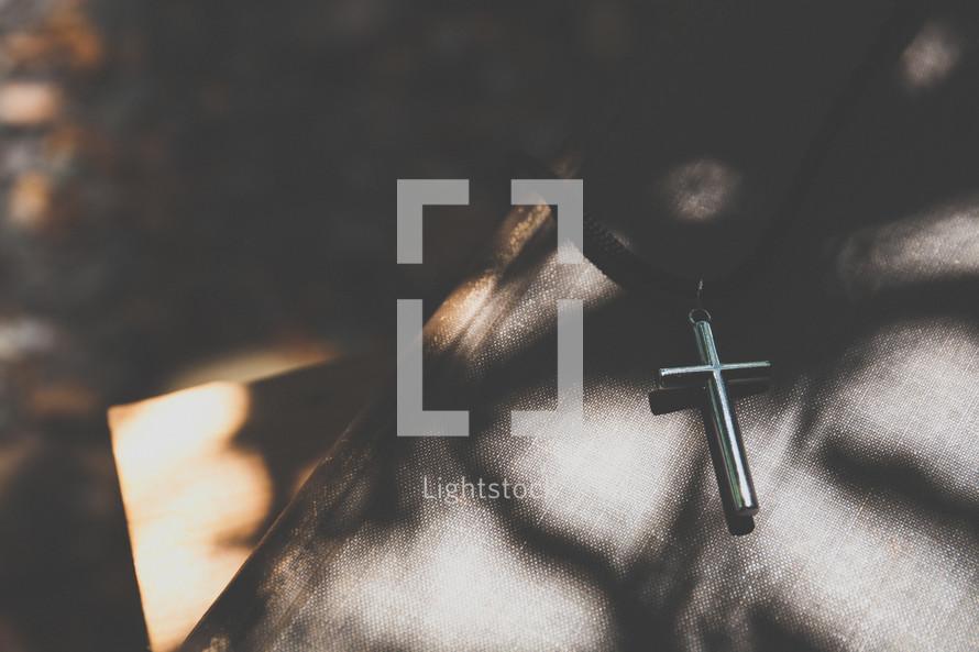 silver cross lying on a Bible