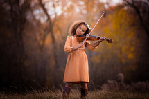 a little girl playing a violin in the woods