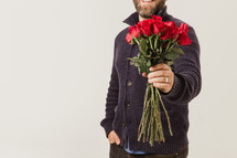man holding long stem roses