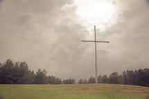 a cross on a hill under an overcast sky