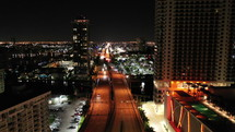 An aerial tilt of nighttime city view over streets in Miami
