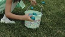 Kids picking up plastic Easter Eggs.