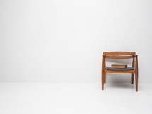 a Bible in a single chair in an empty white room