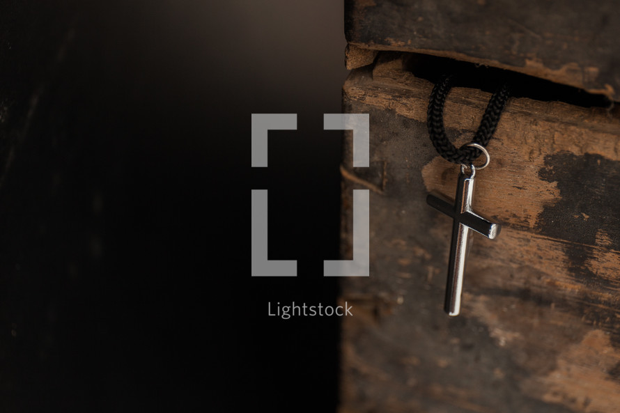cross necklace hanging from a wooden box