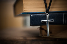 cross necklace on a stack of books