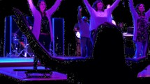 silhouettes of raised hands at a contemporary worship service