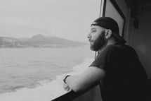 a man with a hat taking in the views on a ferry