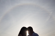 silhouette of a couple forehead to forehead and a sunburst