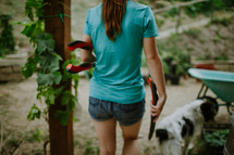 A young woman walking outside with tools for yard work.