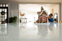 boy and gingerbread house on a kitchen counter