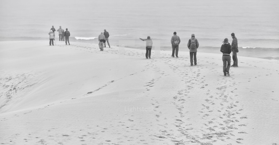 people walking on a beach in winter