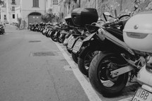 motorcycles and Vespas parked along a street in Italy