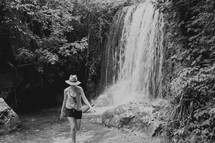 a woman walking in front of a waterfall