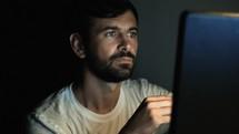 a man staring at a computer screen